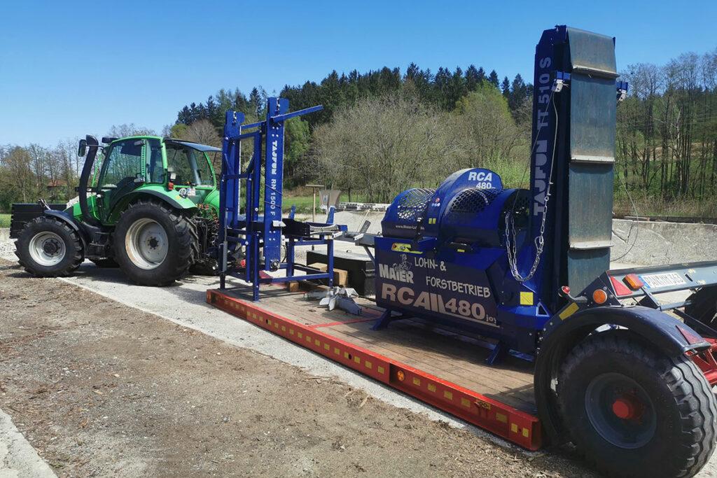 grüner Traktor mit Sägespaltautomat