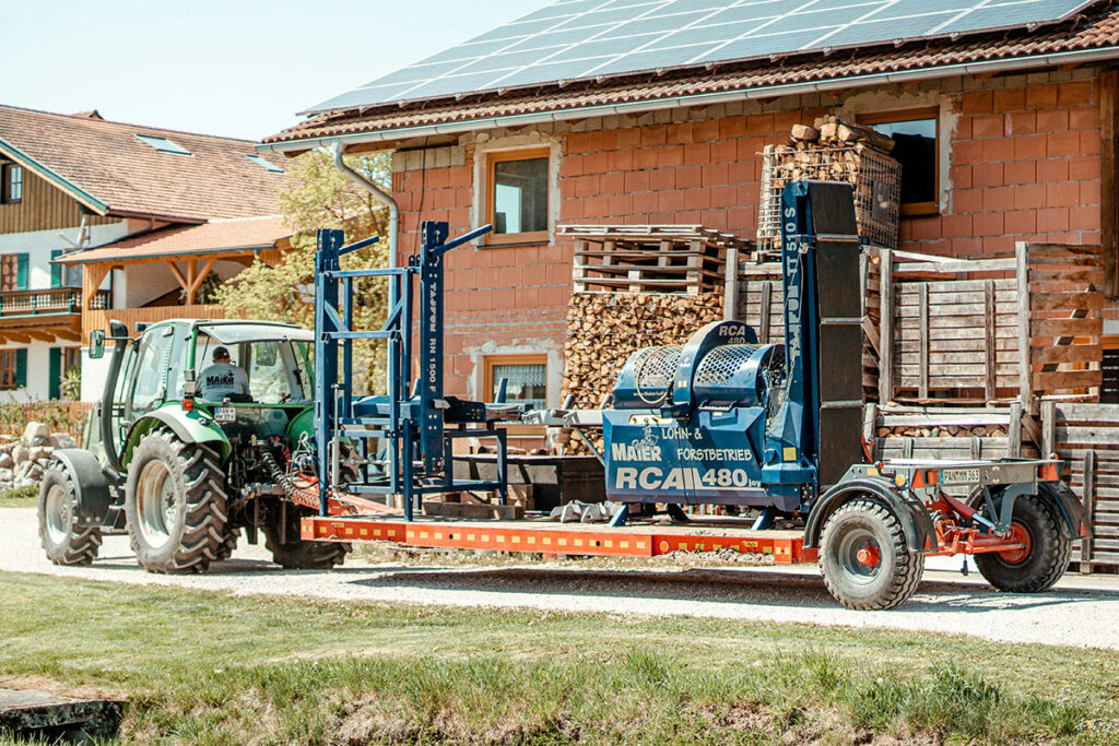 Traktor mit Anhänger und Sägespaltautomat