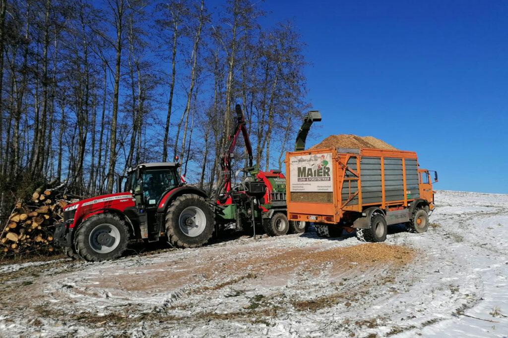 Traktor und LKW, welche Hackschnitzel in einen Anhänger befördern