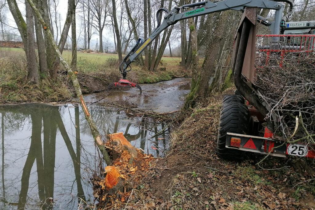 Traktor, der Äste aus einem Fluss holt